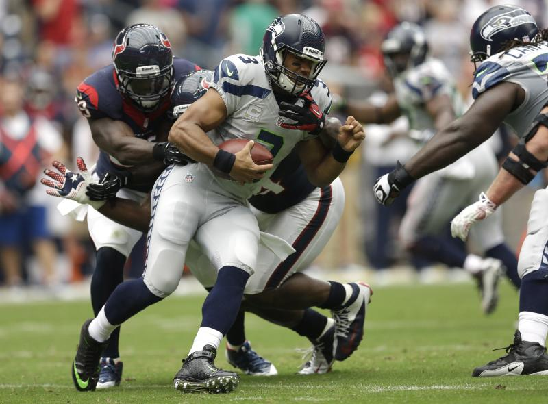Seattle Seahawks quarterback Russell Wilson (3) is taken down during the first quarter an NFL football game against the Houston Texans Sunday, Sept. 29, 2013, in Houston.