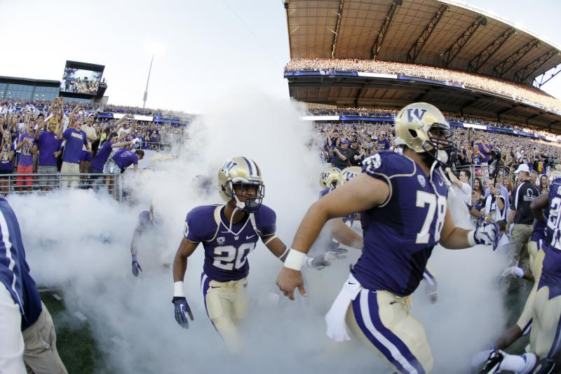 In this photo made with a fish-eye wide angle lens, Washington's Mike Criste (78) and Kevin King (20) run out of the tunnel into newly renovated Husky Stadium for an NCAA college football game against Boise State, Saturday, Aug. 31, 2013, in Seattle.