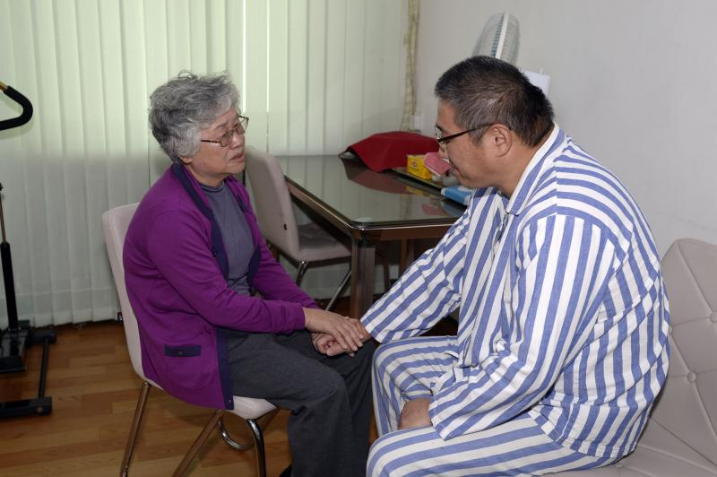 Kenneth Bae, right, an American man detained in North Korea for the past 11 months, and his mother Myunghee Bae talk each other during their meeting at a hospital in Pyongyang Friday, Oct. 11, 2013.
