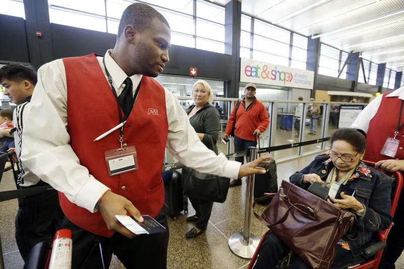 In this Tuesday, Oct. 22, 2013 photo, wheelchair attendant Erick Conley, left, assists an elderly passenger heading overseas at Seattle-Tacoma International Airport in SeaTac, Wash.