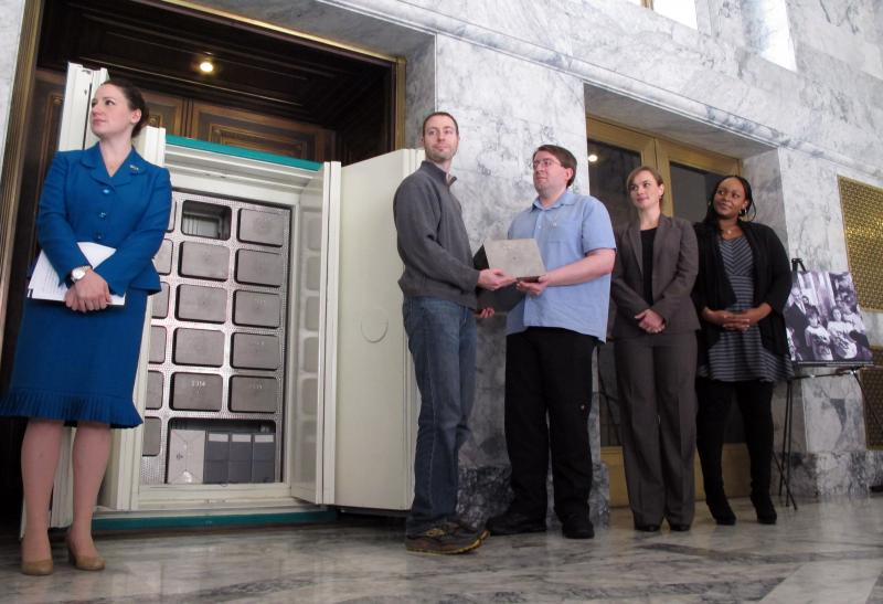 "Volunteer ""keepers"" stand near the opened doors of a safe containing time capsules at the Capitol in Olympia, Wash., on Tuesday, Nov. 12, 2013. The safe contains 16 mini-time capsules which are filled with new items every 25 years, starting in 1989."