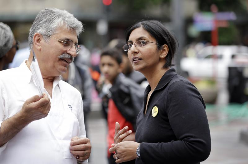 FILE - In this photo taken Aug. 1, 2013, Seattle City Council candidate Kshama Sawant, right, speaks with a restaurant worker during a demonstration in Seattle.