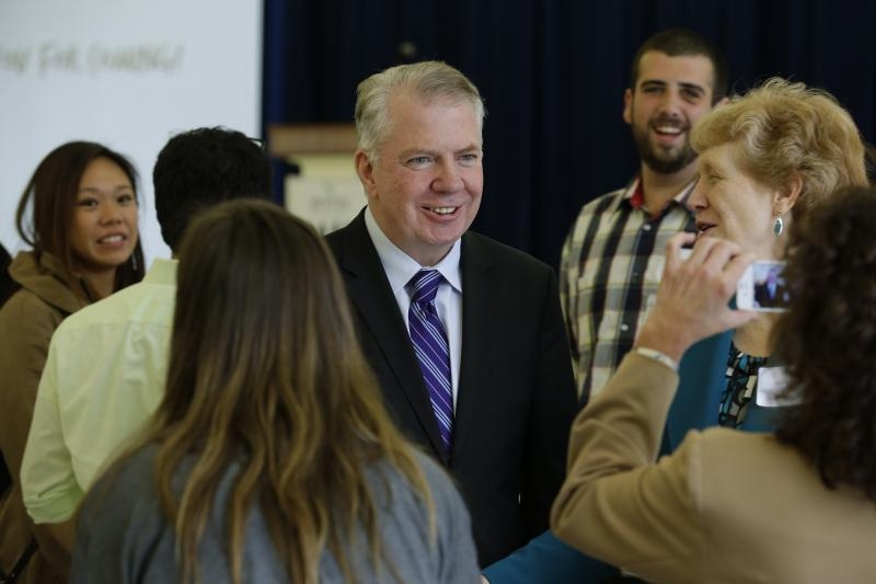 Ed Murray, center, poses for a photo as he visits with guests Wednesday, Nov. 6, 2013 at a fundraising luncheon for ROOTS, a shelter for homeless youth in Seattle.