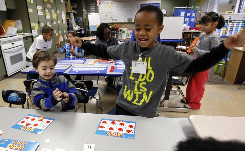 In this photo taken Wednesday, Feb. 6, 2013, Christopher Larry, Jr., right, reacts to winning a letter bingo game as Joel McCain looks on in their kindergarten classroom at Campbell Hill Elementary in Renton, Wash.