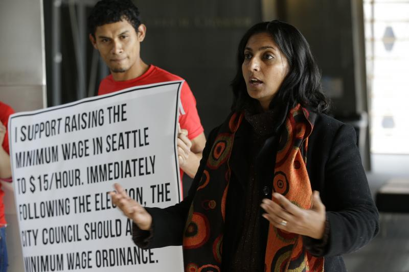 In this photo taken Nov. 4, 2013, Socialist candidate for Seattle City Council Kshama Sawant, right, speaks outside City Council chambers in Seattle.