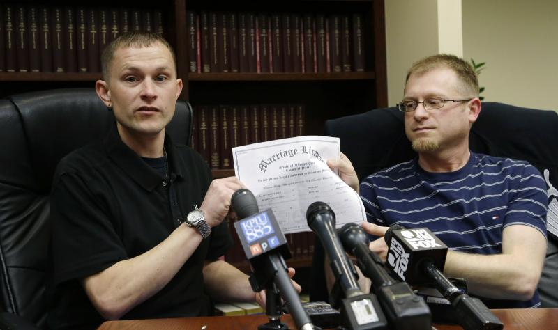 Michael and Eli Hall, right, hold their marriage license certificate, Tuesday, Dec. 3, 2013 as they talk to reporters in Seattle.