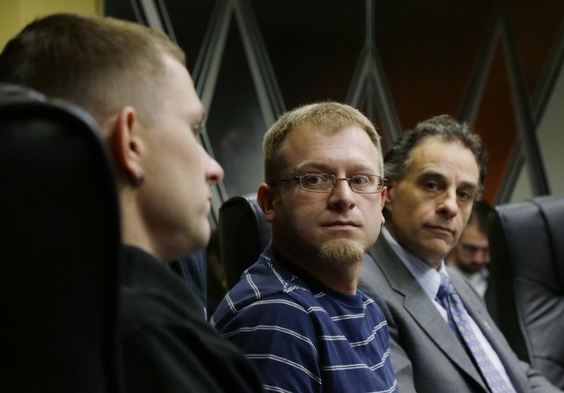 Eli Hall, center, looks on as his husband and BNSF engineer Michael Hall, left, talks to reporters, Tuesday, Dec. 3, 2013, in Seattle.