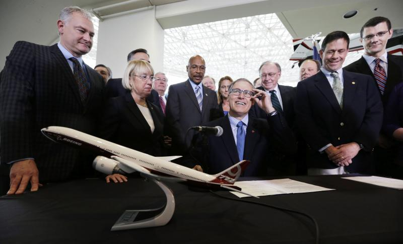 FILE - Gov. Jay Inslee, center, adjusts his glasses as he prepares to sign legislation to help keep production of Boeing's new 777X in Washington, Monday, Nov. 11, 2013, at the Museum of Flight in Seattle.