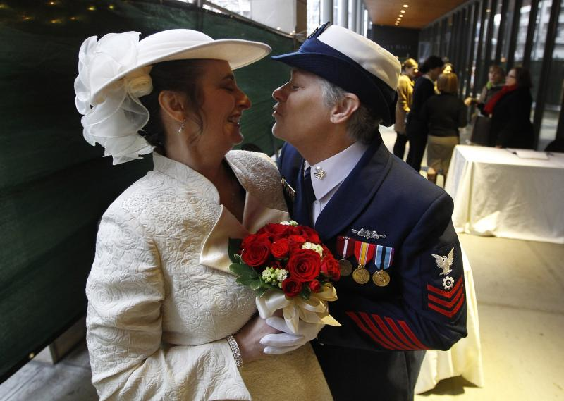 Retired U.S. Coast Guard Petty Officer 1st Class Nancy Monahan, right, wears her dress uniform as she leans to kiss her soon-to-be bride Deb Needham while they wait at Seattle City Hall to become among the first gay couples to legally wed in Washington.