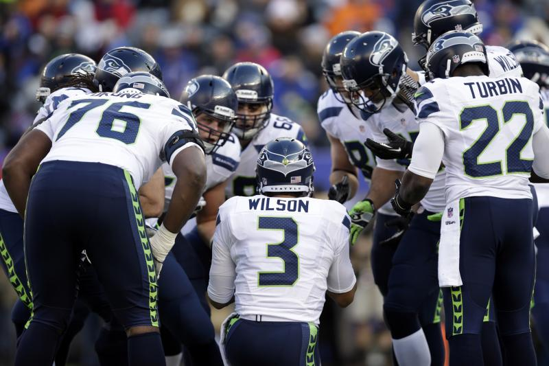 Seahawks quarterback Russell Wilson (3) huddles with teammates.