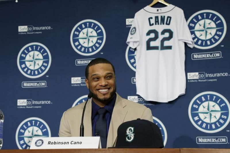 With his new jersey waiting behind him, Robinson Cano smiles as he is introduced as the newest member of the Seattle Mariners baseball team on Thursday, Dec. 12, 2013, in Seattle.