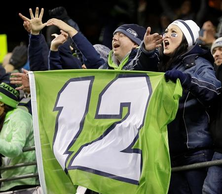 Seattle Seahawks fans cheer as they hold a 12th Man flag in the Monday Night Football match-up against the Saints in Seattle.
