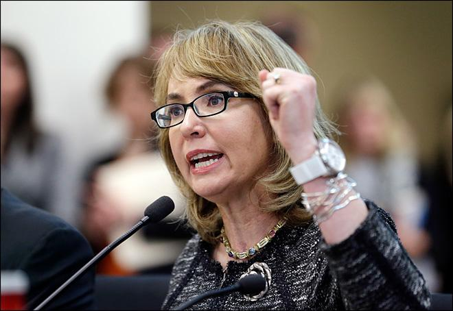 Former Arizona Congresswoman Gabrielle Giffords pumps her fist as she testifies before a Washington state House panel Tuesday, Jan. 28, 2014, in Olympia, Wash.