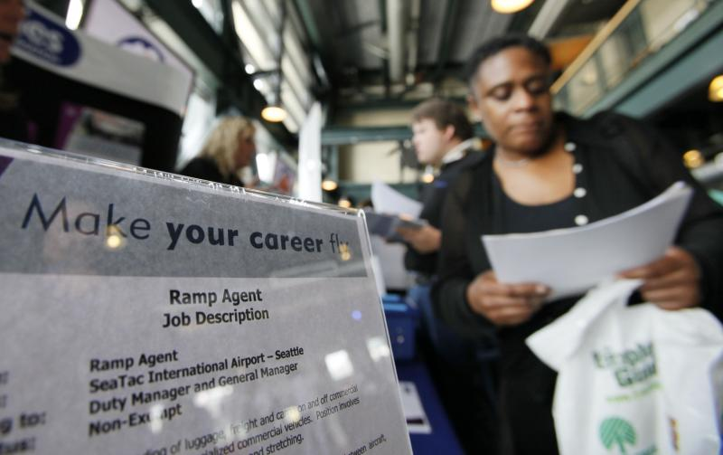 FILE - A woman looks over a job information sheet Tuesday, June 16, 2009, at a job fair in Seattle.