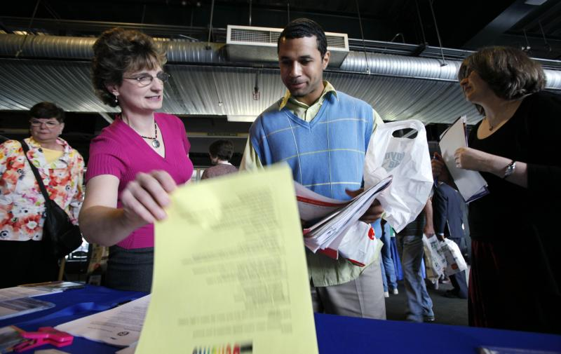 FILE - Internal Revenue Service recruiter Christine Lorbeer, left, goes over employment information with Kris Williams Tuesday, June 16, 2009, at a job fair in Seattle.