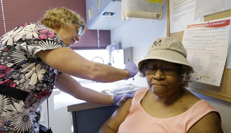 Phyllis Reynolds, right, gets an annual flu shot from medical assistant Judy Davis at a health clinic Tuesday, Oct. 1, 2013, in Seattle.