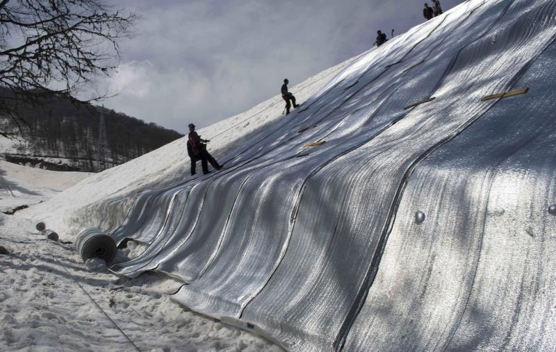 FILE - In this April 5, 2013 file photo, ski resort employees scale down a pile of snow which is being covered by insulated fabric in the Rosa Khutor Alpine center in the mountain cluster in Krasnaya Polyana outside the Black Sea resort of Sochi.