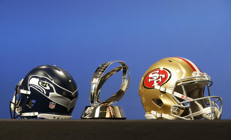 NFL football helmets from the Seattle Seahawks and the San Francisco 49ers are displayed Wednesday, Jan. 15, 2014, along with the George Halas Trophy, which is given to the winner of the NFC championship, during a news conference in Renton, Wash.