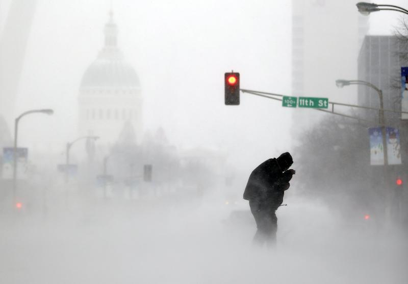 A person struggles to cross a street in blowing and falling snow Sunday, Jan. 5, 2014, in St. Louis.