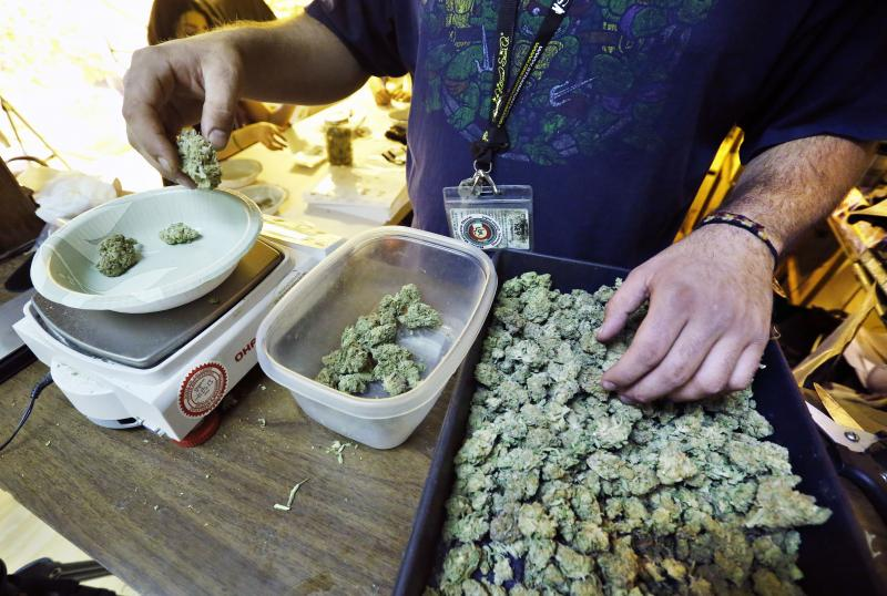 An employee weighs portions of retail marijuana to be packaged and sold at 3D Cannabis Center in Denver, Tuesday Dec. 31, 2013.