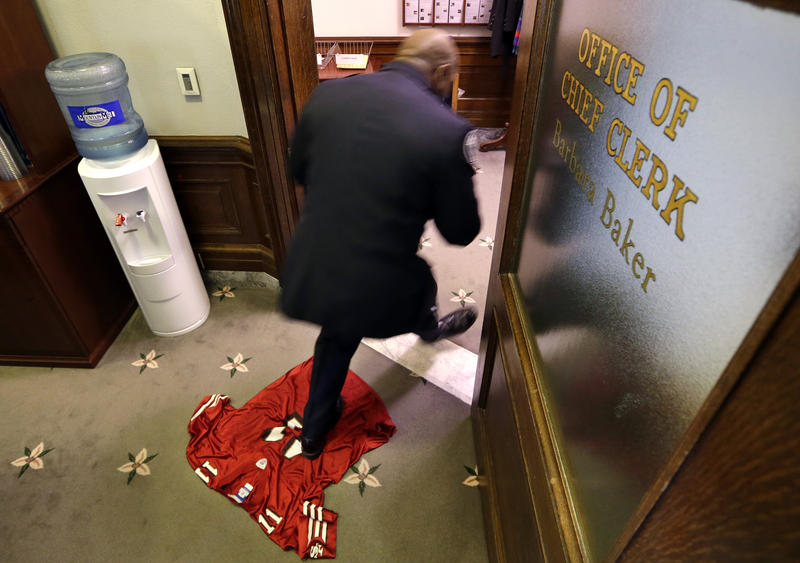 A man walks across a San Francisco 49ers' team jersey on the floor of the House Chief Clerk's office Tuesday, Jan. 14, 2014, in Olympia, Wash.