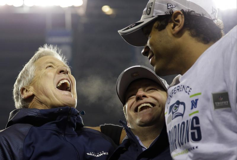 Seattle Seahawks head coach Pete Carroll, left, celebrates with Russell Wilson , right,after the NFL football NFC Championship game against the San Francisco 49ers Sunday, Jan. 19, 2014, in Seattle.