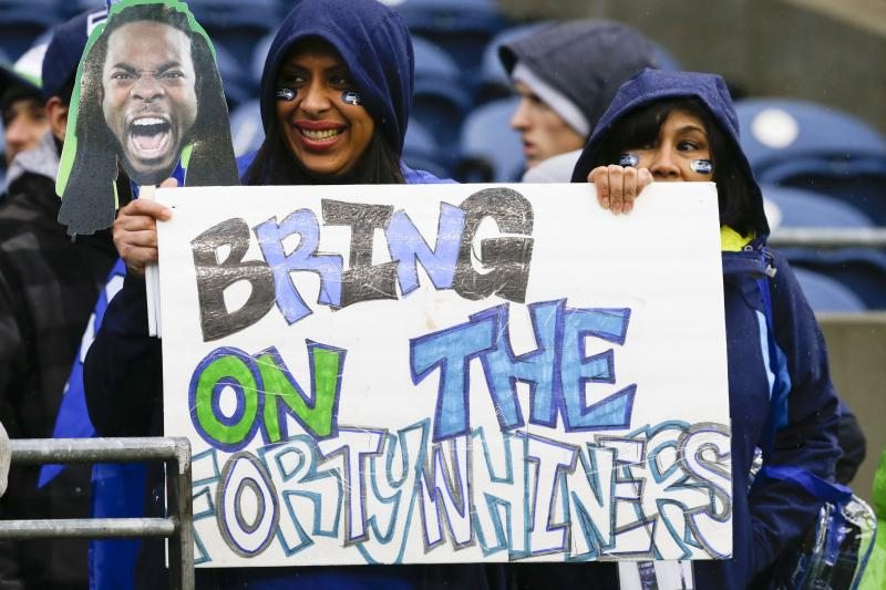 A Seahawks fan holds up a picture of cornerback Richard Sherman and a sign for the San Francisco 49ers before the NFC divisional playoff game between the Seahawks and the New Orleans Saints in Seattle, Saturday, Jan. 11, 2014.