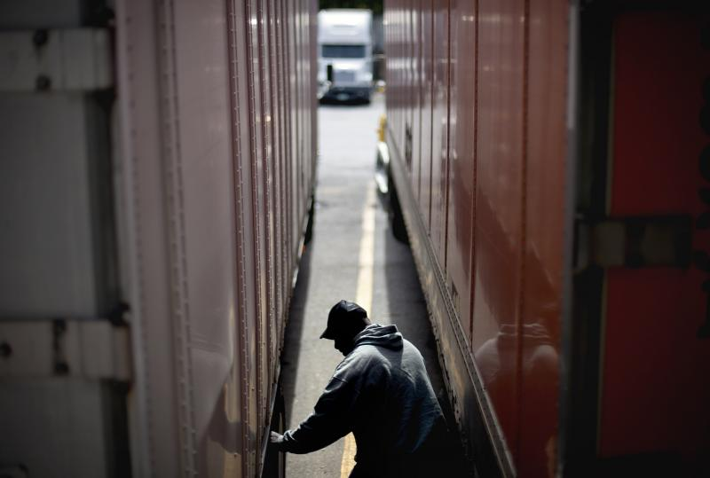 FILE - Truck driver Earliest Madir inspects his truck while waiting for a load at a truck stop Tuesday, Oct. 30, 2012, in Atlanta.