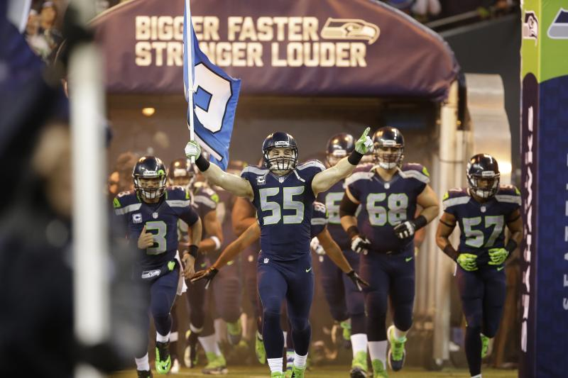 Seahawks' Heath Farwell (55) carries the 12th man flag as he takes the field during player introductions in the Dec. 2 game against the New Orleans Saints in Seattle.