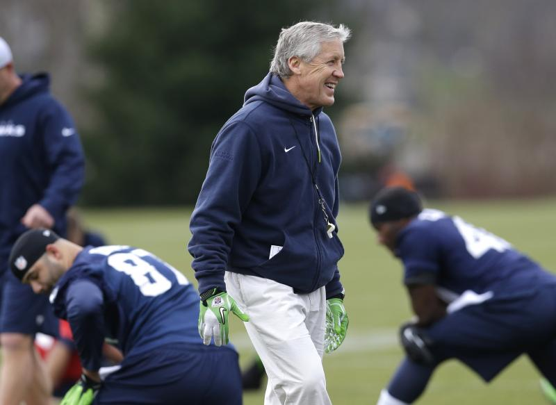 Seattle Seahawks coach Pete Carroll walks on the field as players stretch for NFL football practice Thursday, Jan. 2, 2014, in Renton, Wash.