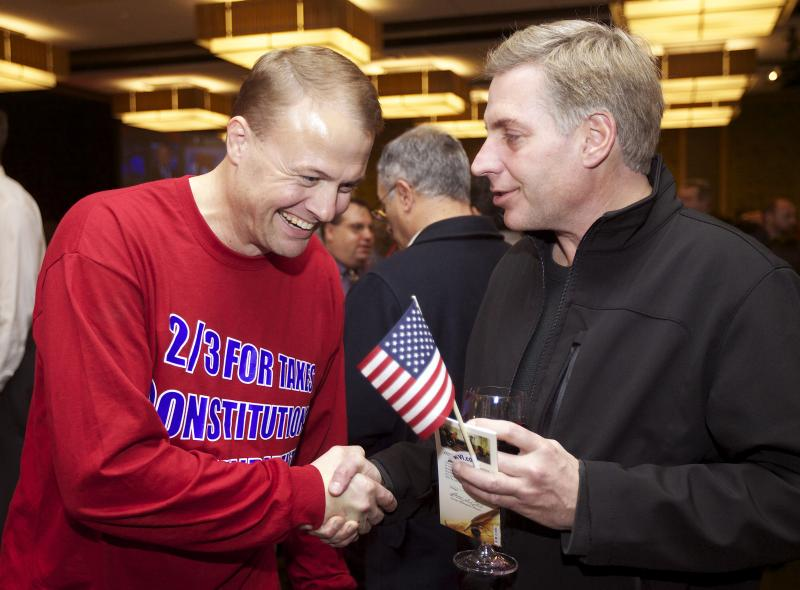 FILE - In this Nov. 6, 2012, file photo, professional initiative promoter Tim Eyman shakes hands with a supporter in Bellevue, Wash.
