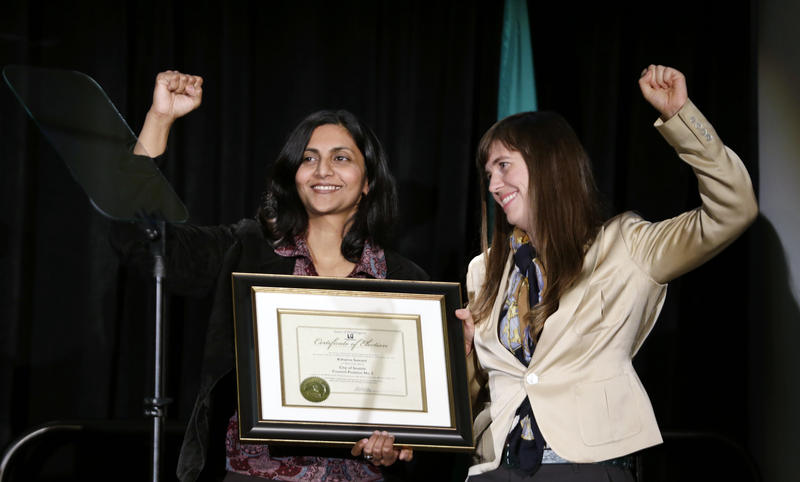 New Seattle Seattle Council member Kshama Sawant, left, holds up a clenched fist as she stands with Nicole Grant, who assisted in a ceremonial swearing-in, at an inaugural event Monday, Jan. 6, 2014, in Seattle.