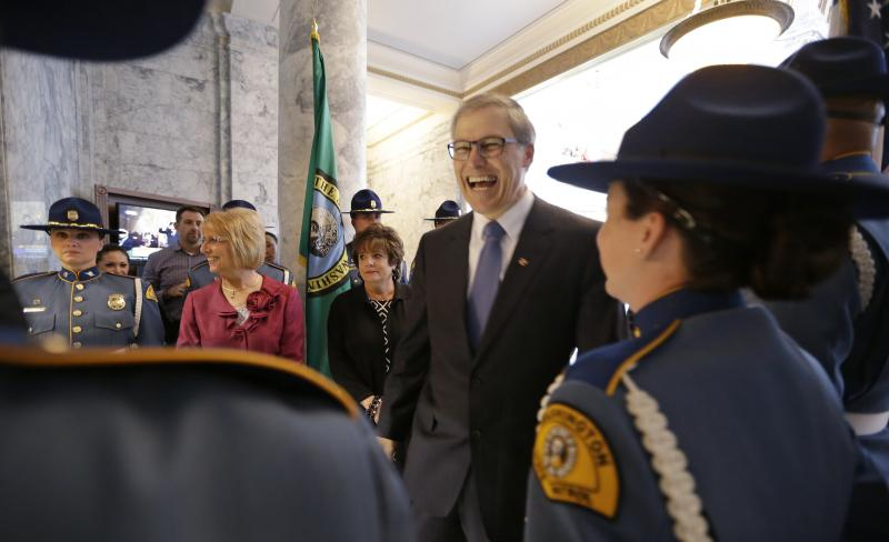Gov. Jay Inslee, center, smiles as he greets State Patrol troopers outside the House chambers before entering to give the annual State of the State address to a joint session of the Legislature Tuesday, Jan. 14, 2014, in Olympia, Wash.