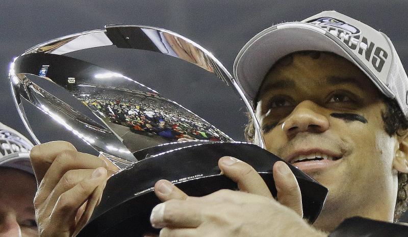 Seattle Seahawks' Russell Wilson holds up the George Halas Trophy after the NFL football NFC Championship game against the San Francisco 49ers, Sunday, Jan. 19, 2014, in Seattle.