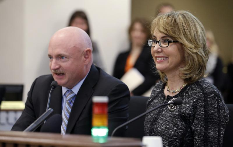 Former Arizona Congresswoman Gabrielle Giffords, right, smiles briefly as her husband, retired NASA space shuttle commander Mark Kelly, testifies before a Washington state House panel Tuesday, Jan. 28, 2014, in Olympia.