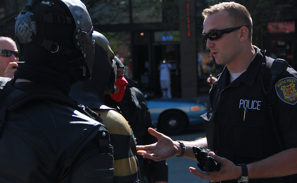 A Seattle police officer is seen talking to Phoenix Jones and his sidekicks.