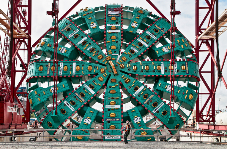 Suspended from a towering gantry crane, the SR 99 tunneling machine's 57.5-foot-diameter cutterhead hangs for its last hours above ground before being lowered into the launch pit.