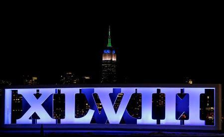 The Empire State Building – in Seahawks blue and green – backdrops a sign for Super Bowl XLVIII in Hoboken, N.J., this week.