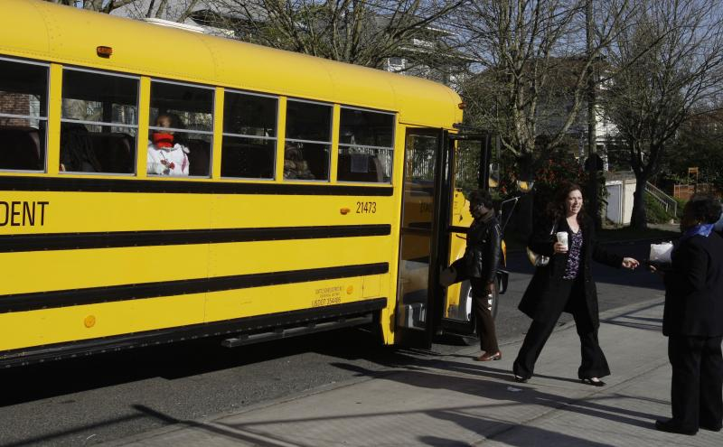 FILE - School officials talk to the driver of a school bus about several students on board a bus outside the Madrona K-8 school Thursday, April 30, 2009, in Seattle.