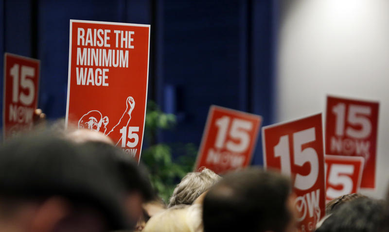 FILE - Signs supporting a $15 minimum wage are held up at an inaugural event for new Seattle City Council members, city attorney and may Monday, Jan. 6, 2014, in Seattle.