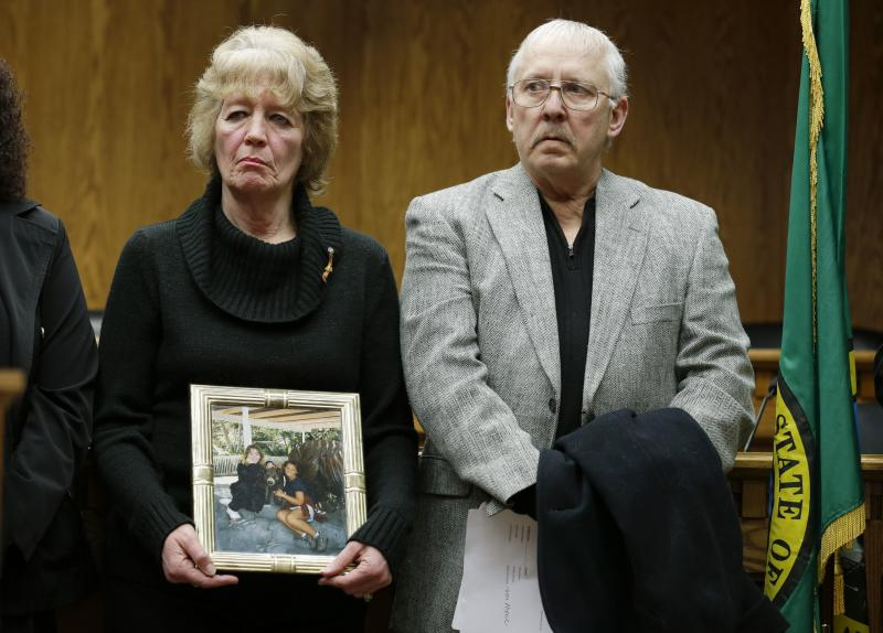 Sherry Shaver, left, holds a photo of her two daughters, Venus, left, and Telisha, right, as she stands with her husband Roger Shaver, right, Wednesday, Feb. 26, 2014, during a news conference at the Capitol in Olympia, Wash.