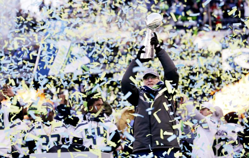 Seattle Seahawks owner Paul Allen lifts the Vince Lombardi Trophy during a rally on Wednesday, Feb. 5, 2014, in Seattle.