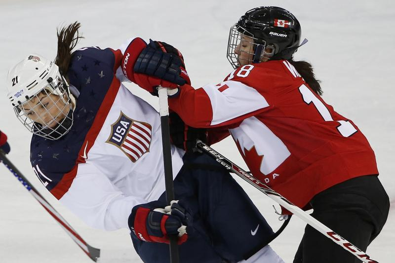 Hilary Knight of the United States collides with Catherine Ward of Canada during the first quarter of the 2014 Winter Olympics women's ice hockey game at Shayba Arena, Wednesday, Feb. 12, 2014, in Sochi, Russia.