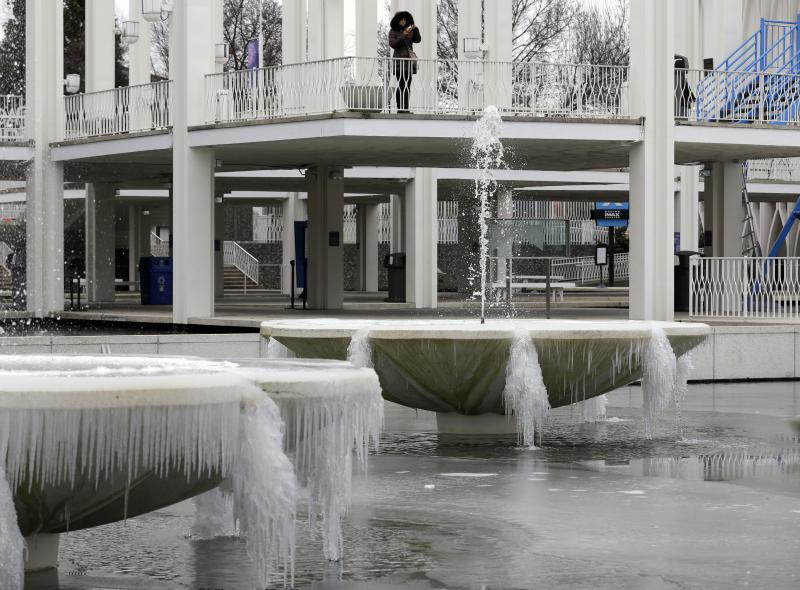 A visitor photographs frozen fountains caked with ice at the Pacific Science Center in Seattle, Thursday, Feb. 6, 2014.