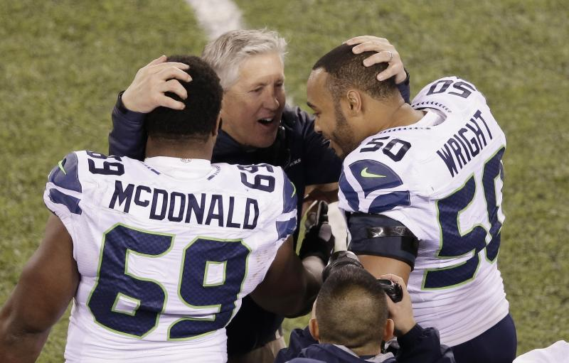 Seattle Seahawks head coach Pete Carroll embraces Clinton McDonald manx K.J. Wright after the second half of the NFL Super Bowl XLVIII football game against the Denver Broncos, Sunday, Feb. 2, 2014, in East Rutherford, N.J.