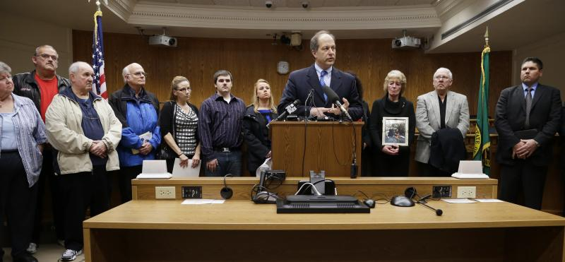 Sen. Steve O'Ban, center, R-University Place, stands in front of a group of family members of murder victims, Wednesday, Feb. 26, 2014, during a news conference at the Capitol in Olympia, Wash.