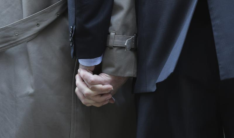 File - Mark Phariss, left, clutches the hand of partner Victor Holmes, right, as they talk to the media outside the U.S. Federal Courthouse on Wednesday, Feb. 12, 2014, in San Antonio.