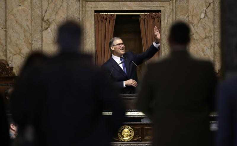Spectators look in from outside the House chambers as Gov. Jay Inslee waves during the annual State of the State address to a joint session of the Legisture Tuesday, Jan. 14, 2014, in Olympia, Wash.