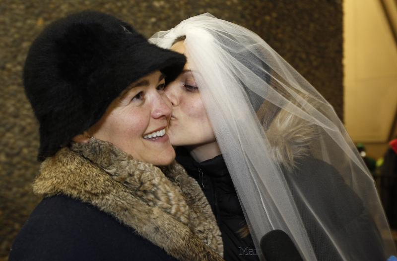 Amy Andrews, right, smiles as she wears a veil while kissing her partner Jeri Andrews while waiting to be among the first to be issued a marriage licenses to a same-sex couple, Wednesday, Dec. 5, 2012, in Seattle.
