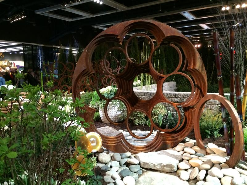 "This show garden, called ""Circles All Around Us,"" uses iron circle forms and plants that are round in shape or with round leaves or flowers."